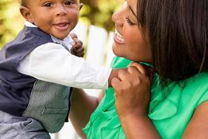 afroamerikanische Mutter, die ihren Sohn hält.