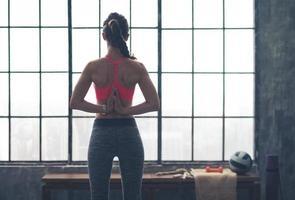 Frau mit den Händen hinter dem Rücken in Yoga-Pose gefaltet foto