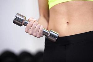 Nahaufnahme der Frau im Fitnessstudio, die freie Gewichte hebt