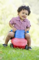 Junge, der auf Spielzeug mit Rädern im Freien spielt foto