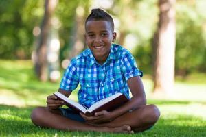 Außenporträt des schwarzen Jungen des Studenten, der ein Buch liest