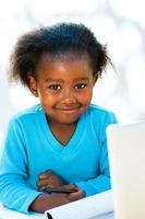 niedlicher afrikanischer Student, der Hausaufgaben macht. foto