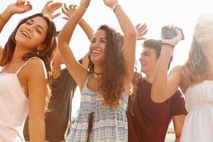 Gruppe von jugendlichen Freunden, die draußen gegen Sonne tanzen foto