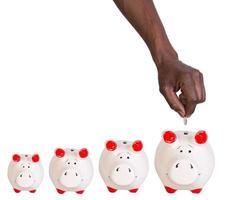 männliche Hand, die eine Münze in ein Sparschwein legt