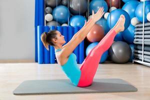 Pilates Teaser Übung Frau auf Matte Gym Indoor