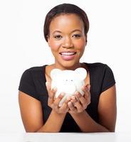junge Afroamerikanerfrau, die Sparschwein hält foto