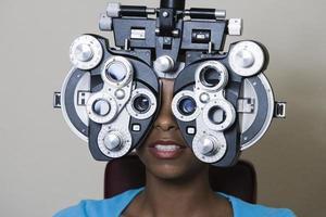 Afroamerikanerfrau, die ihre Vision überprüfen lässt foto
