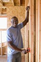 Mann, der Wand in teilweise gebautem Haus misst, lächelnd, Porträt foto