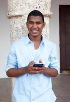 junger Mann in einem blauen Hemd, das Nachricht am Telefon schreibt