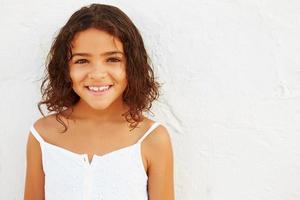 lächelndes junges Mädchen, das draußen gegen weiße Wand steht foto