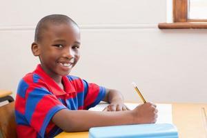 niedlicher Schüler, der Kamera im Klassenzimmer lächelt foto