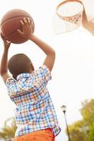 Junge auf Basketballplatz, der für Korb schießt foto