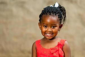 kleines afrikanisches Mädchen mit geflochtener Frisur.