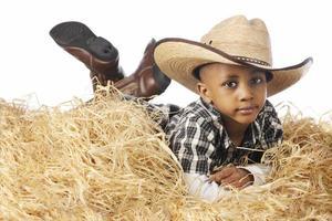 junger Cowboy, der sich im Stroh entspannt foto