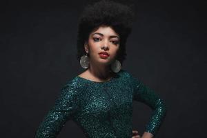 Afroamerikanerfrau im grünen Kleid mit den Händen auf Taille.