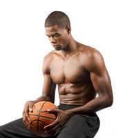 Afroamerikaner Mann sitzt hält Basketball schaut nach unten foto