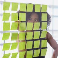 Porträt einer Geschäftsfrau mit einem Afro hinter klebrig foto
