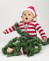 Weihnachtsbaby in Girlande gewickelt