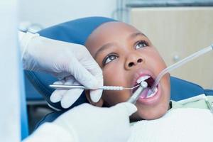 Junge, dessen Zähne vom Zahnarzt untersucht werden foto