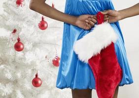 Rückansicht der Frau, die Weihnachtsstrumpf hält foto