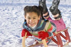 aufgeregtes Mädchen, das schneebedeckten Hügel auf Schlitten hinunterrodelt