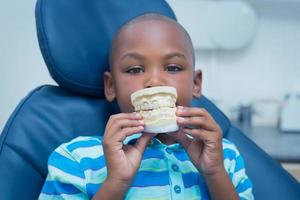 Porträt des lächelnden Jungen, der Mundmodell hält foto