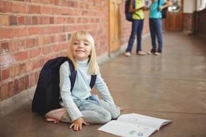 niedlicher Schüler, der über Notizblock am Korridor kniet foto