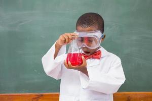 Überraschungsschüler, der eine rote Flüssigkeit betrachtet