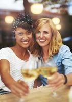lustige Freunde, die mit Weißwein feiern foto