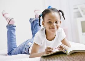 glückliches Mädchen, das im Buch färbt