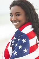 afroamerikanerin in usa flagge am strand foto