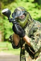 Paintballspieler, der mit der Waffe zielt foto