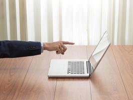 Geschäftsmannhand, die auf Laptop zeigt foto