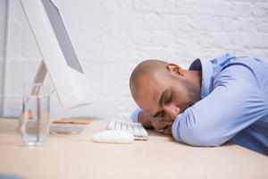 Geschäftsmann, der durch Computer am Schreibtisch schläft