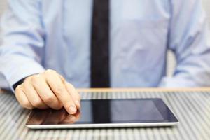 Geschäftsmann mit Tablet-Computer auf dem Schreibtisch