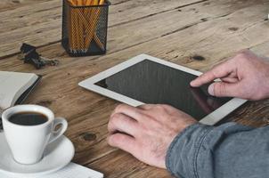 Mann, der im Büro mit Tablet-Computer arbeitet foto