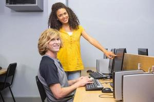 Schüler, die im Klassenzimmer am Computer arbeiten foto