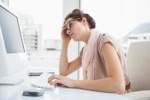 fokussierte Geschäftsfrau mit Brille am Computer