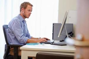 männlicher Arzt im Büro, der am Computer arbeitet foto