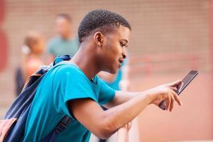 männlicher afrikanischer Student, der Tablet-Computer verwendet