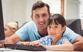 süßer Schüler in der Computerklasse mit Lehrer