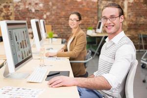 lächelnde Bildbearbeiter, die Computer im Büro verwenden foto
