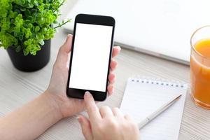 Frauenhand, die Telefon mit isoliertem Bildschirm über dem Schreibtisch hält
