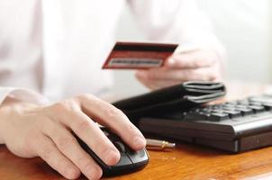 Hände des Geschäftsmannes mit Geldbörse und Bankkarte auf der
