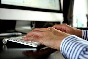 Mann tippt auf der Tastatur foto