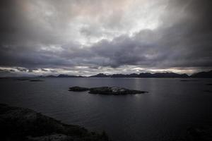 Lofoten Norwegen bewölkter Meerblick mit kleinen Felseninseln - dunkel foto