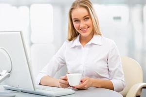 junge Geschäftsfrau, die Computer im Büro benutzt foto