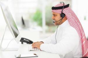 Geschäftsmann aus dem Nahen Osten, der an einem Computer arbeitet foto