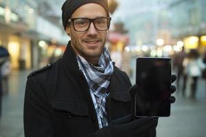 städtischer Mann hält Tablet-Computer auf der Straße foto