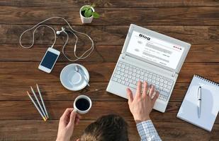 Schriftsteller, der am Computer am hölzernen Schreibtisch arbeitet foto